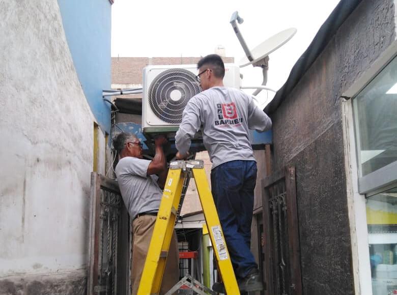 Técnicos instalando equipos de aire acondicionado